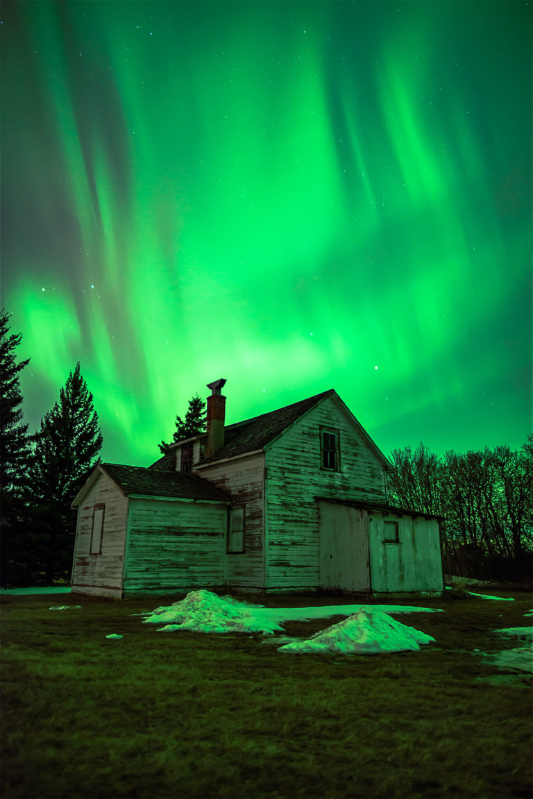 Aurora Borealis dances over an abandoned house in the Saskatchewan landscape