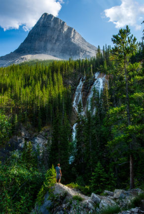 A man standing in front of a mountain peak and waterfall in the Alberta Landscape