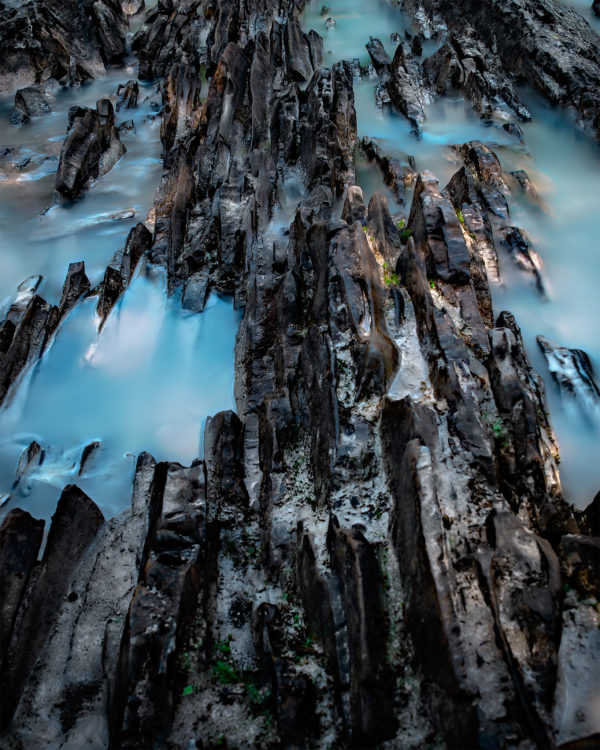 An abstract photograph of a rocky ridge in a glacial river
