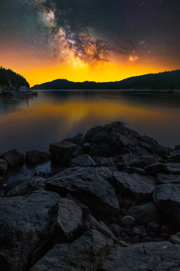Landscape astrophotography in British Columbia on Gambier Island. The milky way rises above the ocean coastline