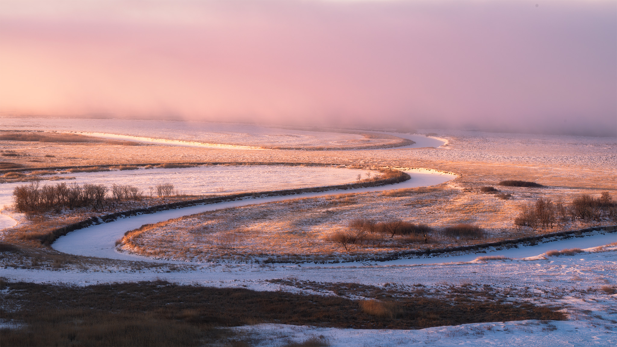 Light hits the Saskatchewan landscape as a frozen river winds through the scene