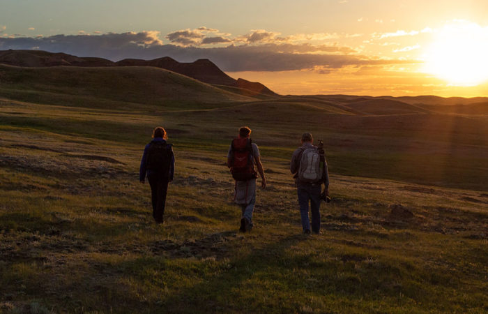 Three students participating in a landscape photography workshop in Grasslands National Park, Saskatchewan.