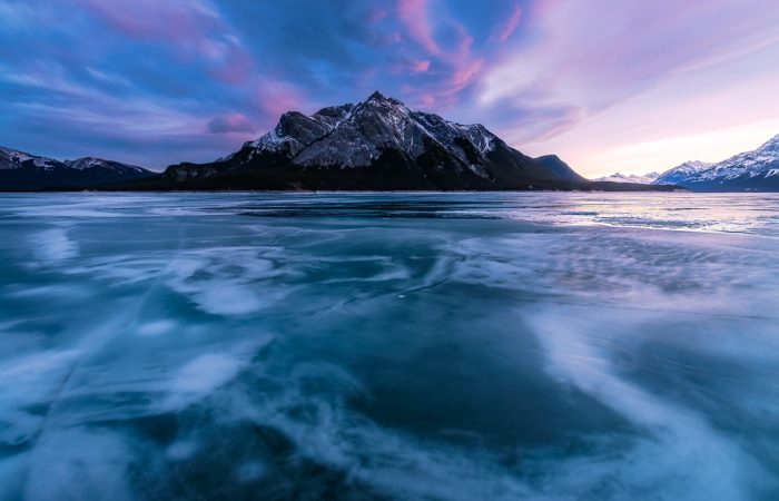Landscape photography in the Canadian Rockies in winter. Ice shapes lead to Mt. Mitchener on Abraham Lake