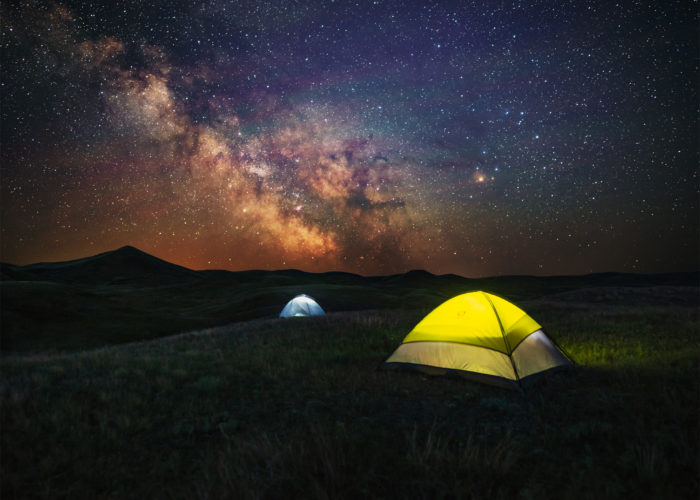 Landscape astrophotography of the milky way and two tents under the milky way in Grasslands National Park, Saskatchewan