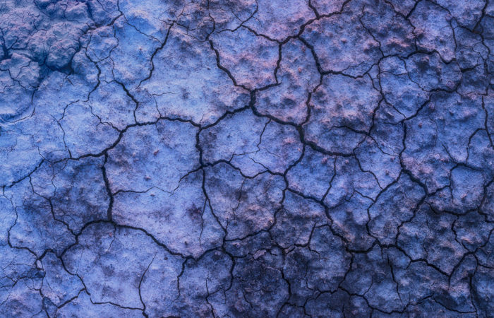 Abstract photography of mud cracks in Saskatchewan reflecting twilight colours.