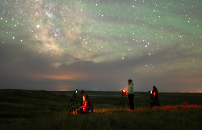 Students participating in a night photography workshop with the milky way in front of them