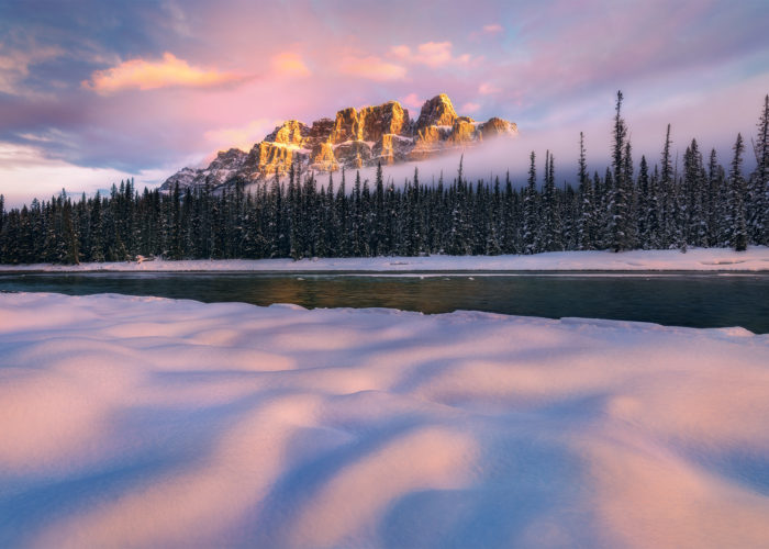 A landscape photograph of a beautiful sunrise at Castle Mountain in the winter
