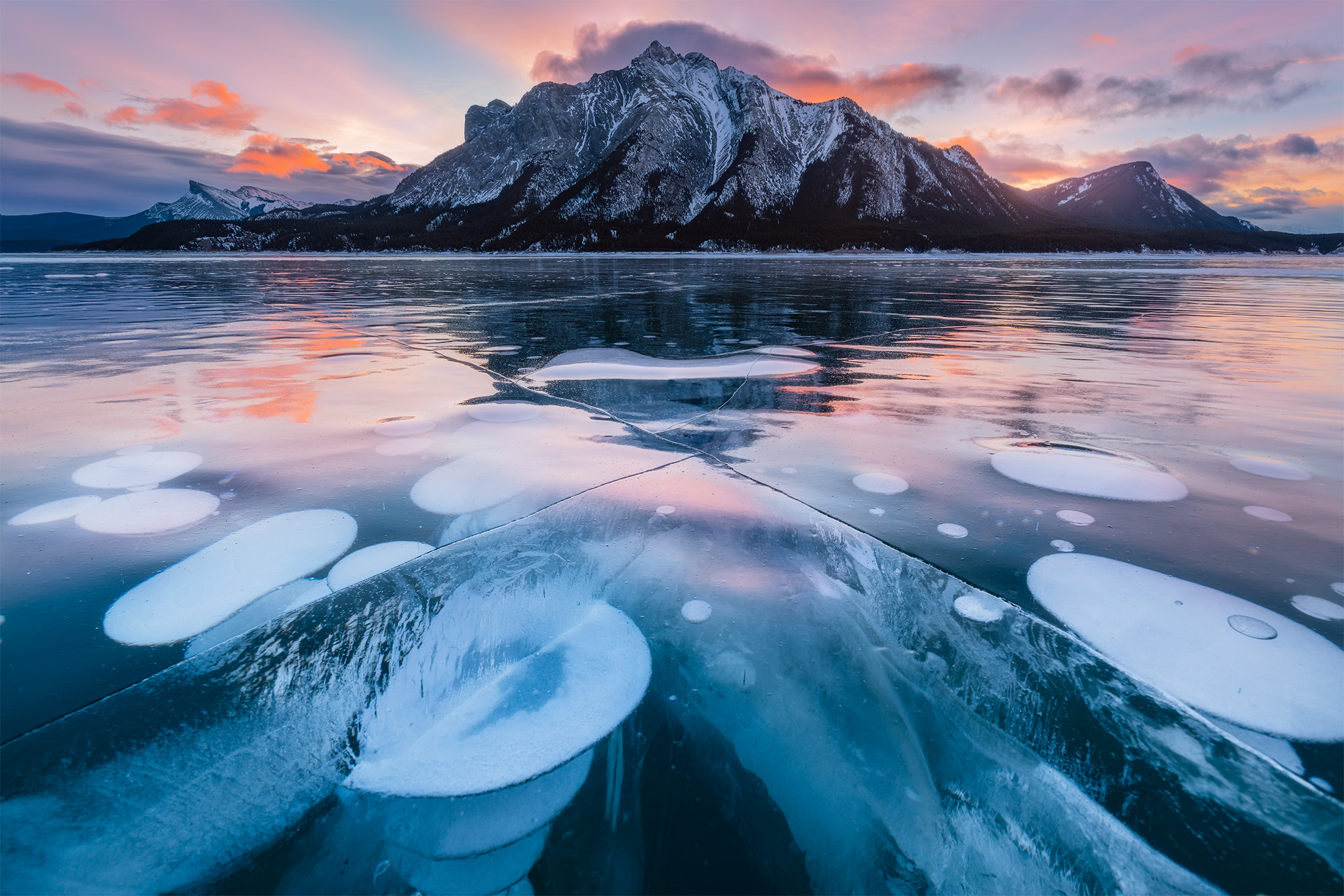 A landscape photograph of methane bubbles on abraham lake during sunrise in the winter