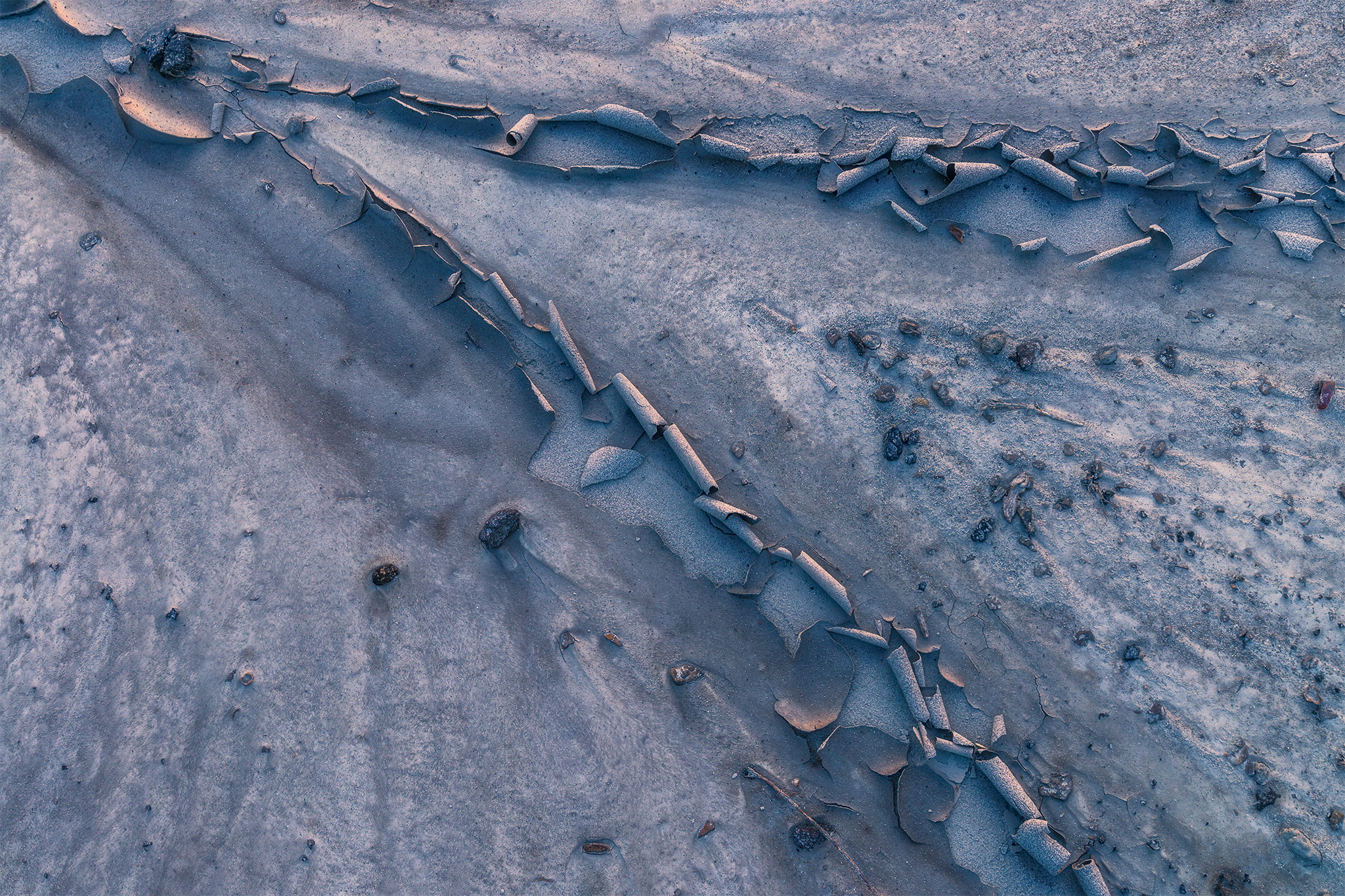 an intimate landscape photograph of cracked white clay reflecting sunset colours
