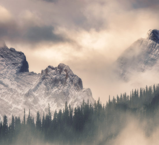 An intimate landscape photograph of two mountains surrounded in light and clouds in the Canadian Rockies