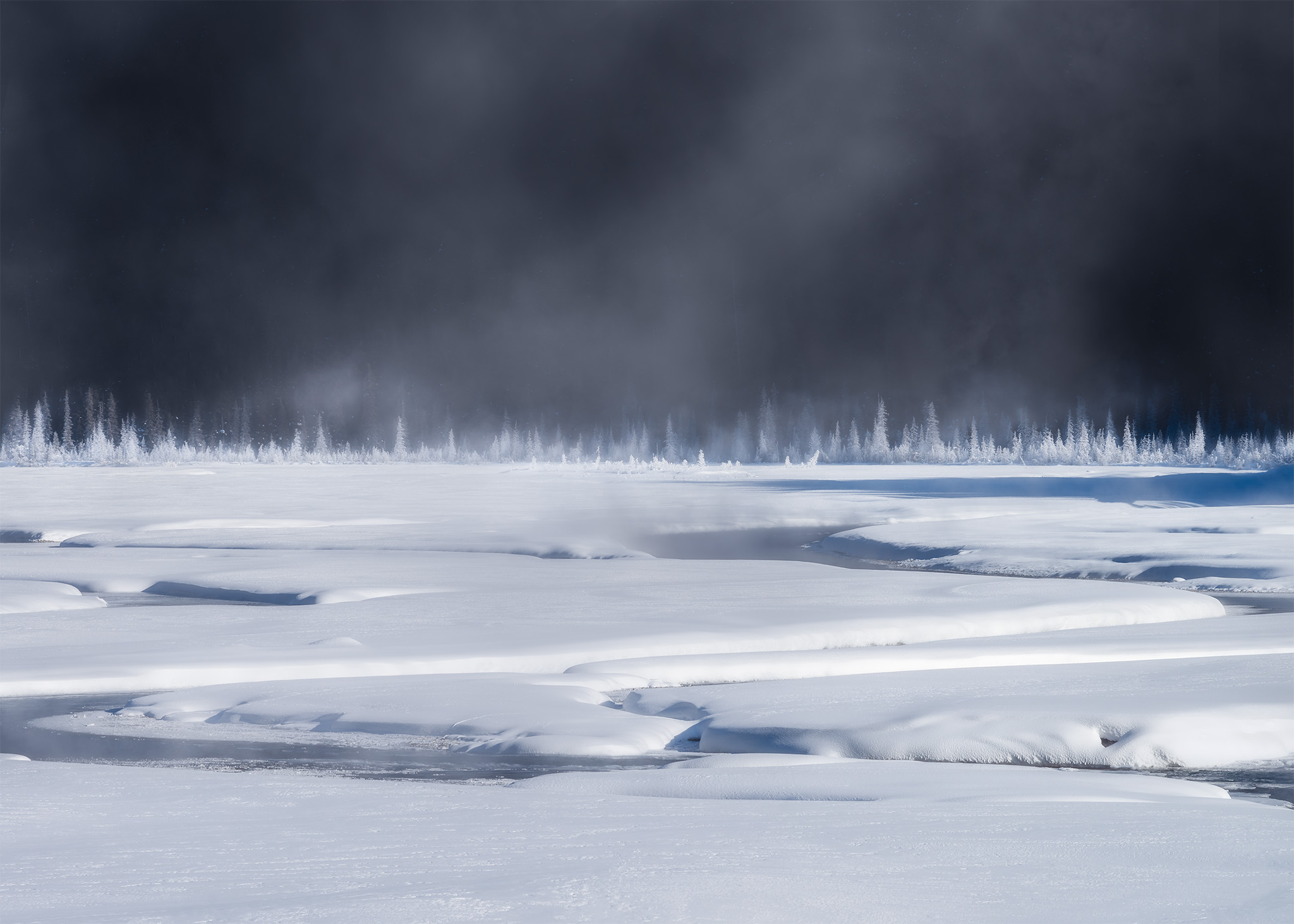 An intimate landscape photograph of the Candian Rockies on a cold winter morning that created steam on the river