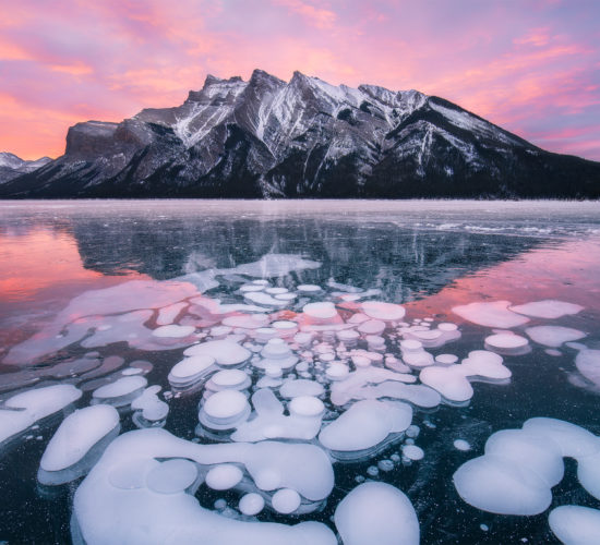 Sunrise photograph of Lake Minnewanka during winter with frozen bubbles