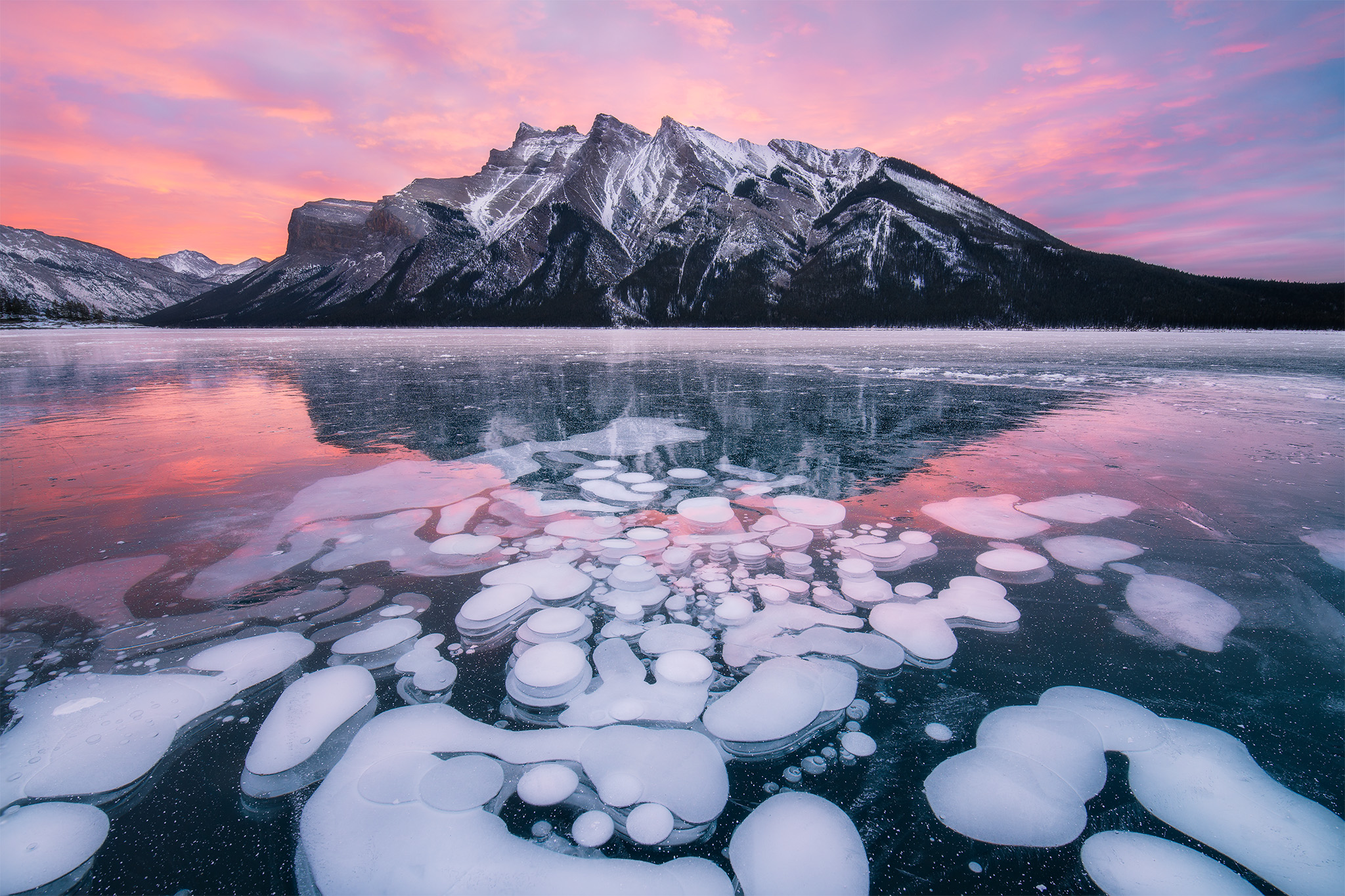 Sunrise photograph of Lake Minnewanka during winter with frozen bubbles