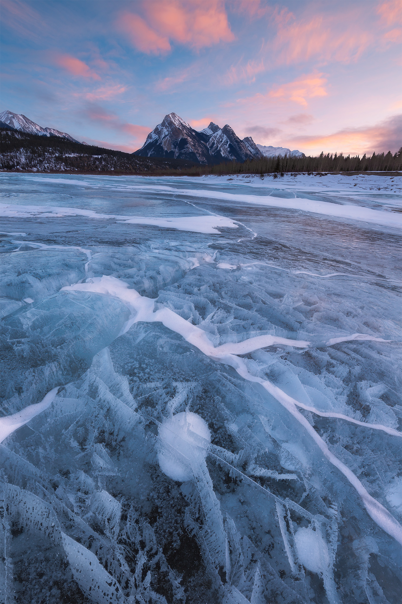 A landscape photograph of Ex Coelis Mountain on Abraham Lake with bubbles and ice textures