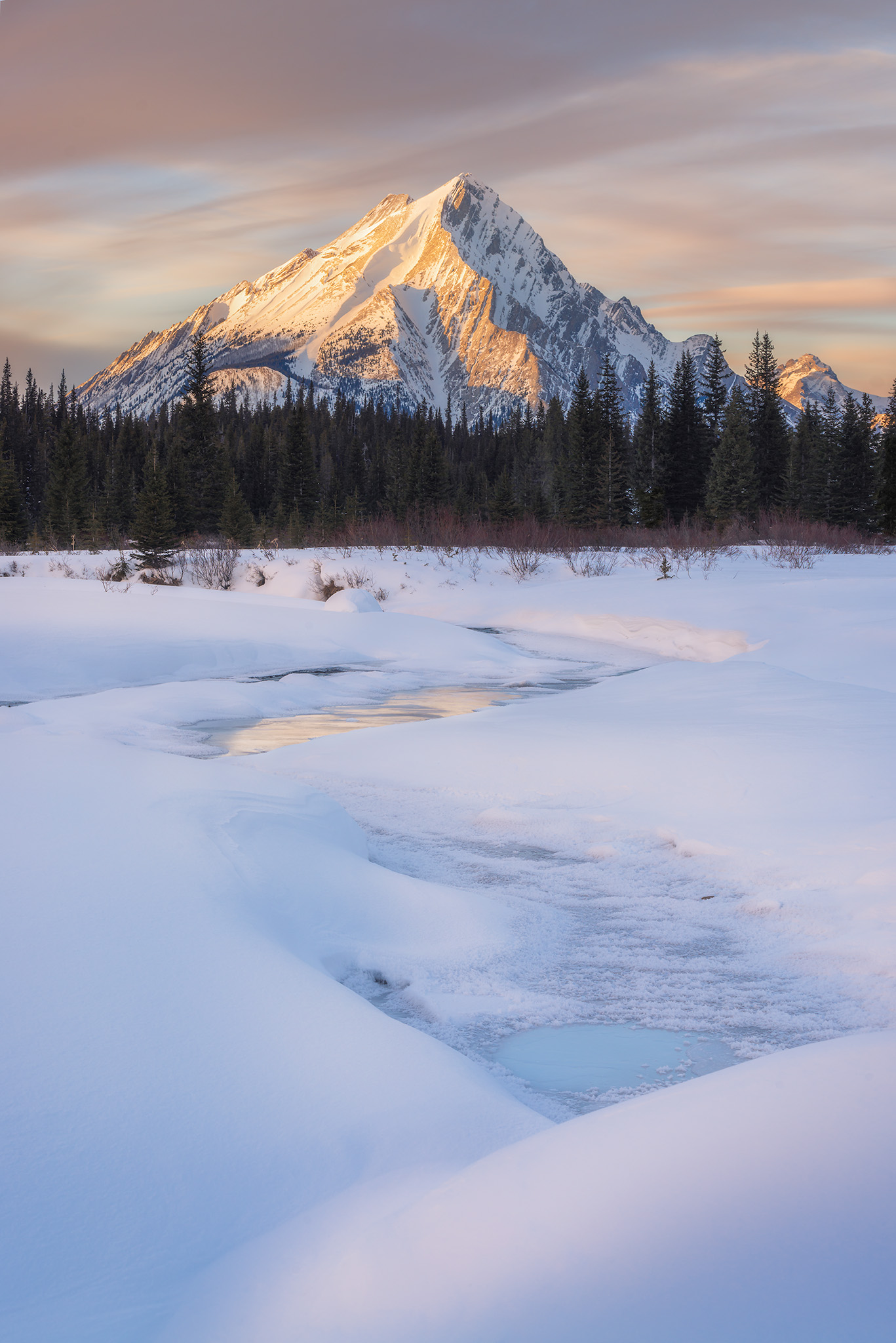 A landscape photograph of a mountain bathed in sunset light in the Canadian Rockies