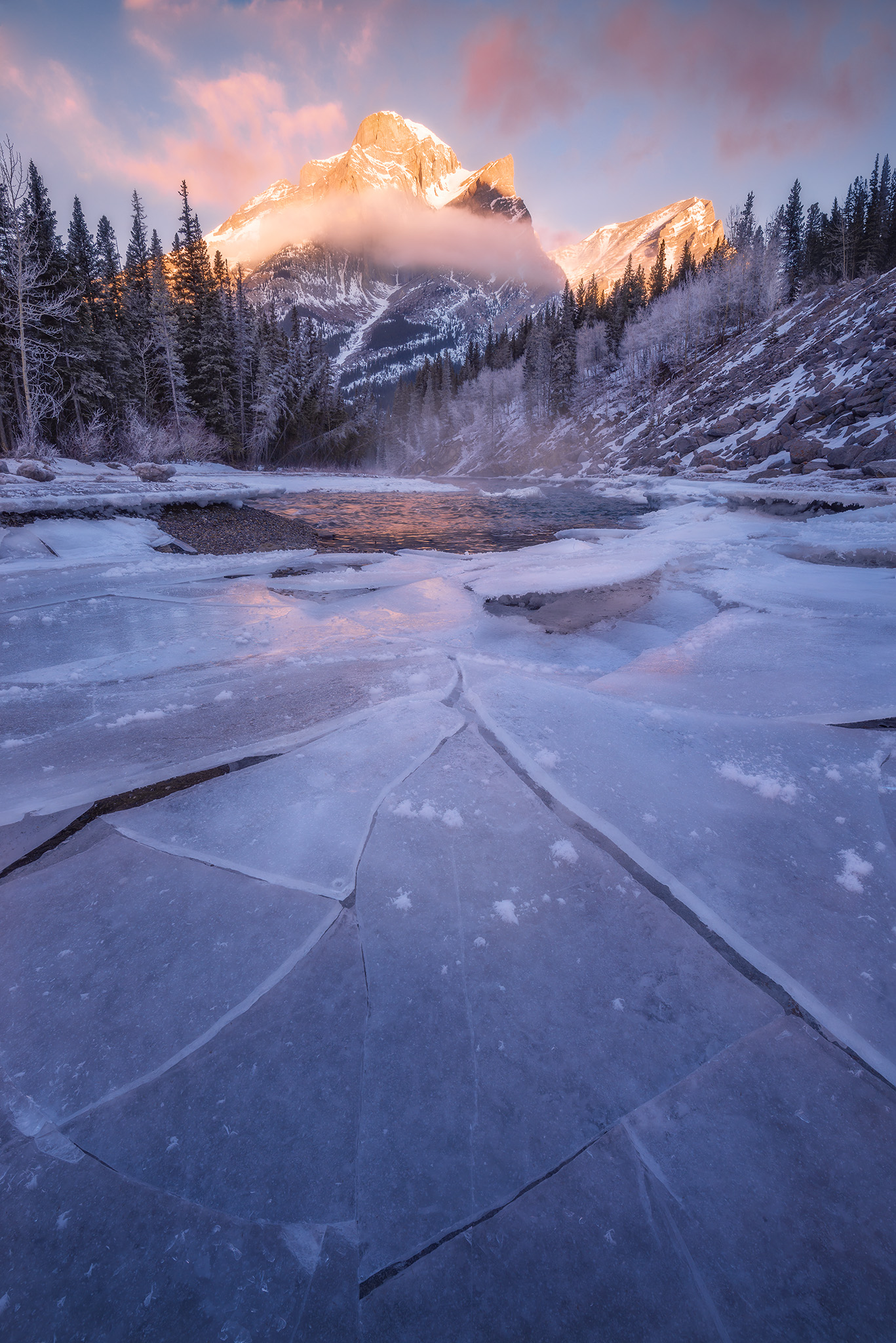 A landscape photograph of Mount Kidd at sunrise in winter in the Canadian Rockies